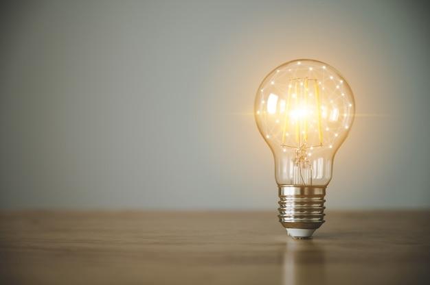 Лампочка на деревянном столе с копией пространства. концепция вдохновения творческой идеи мышления и будущих технологических инноваций