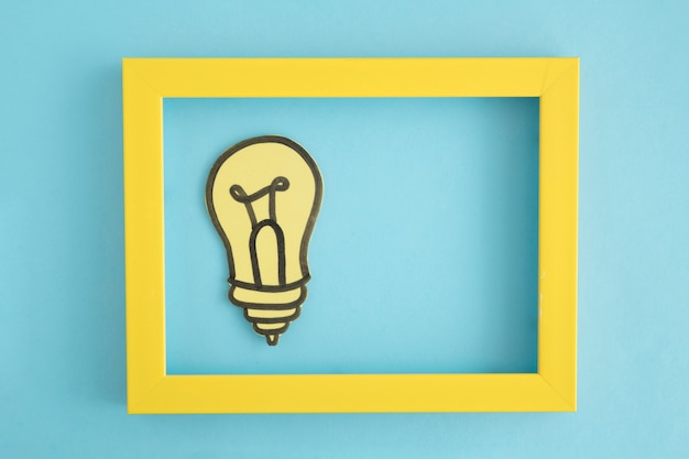 Light bulb paper cutout in the yellow border frame on blue background