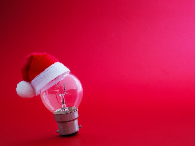 Light bulb and santa claus hat over red background with copy space.