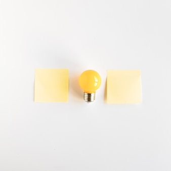 Light bulb between two adhesive notes on white background