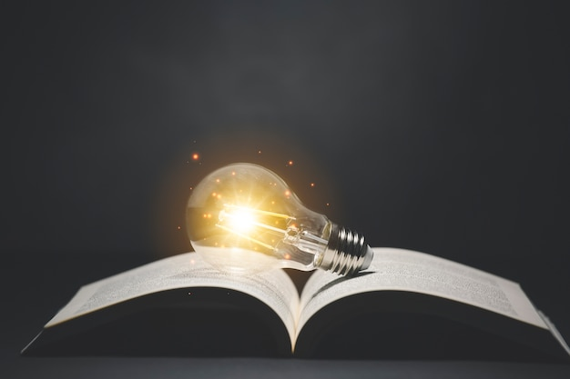 Light bulb and  vintage book with blurred lights