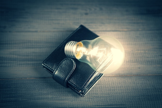 Light bulb on a wallet on a wooden gray table