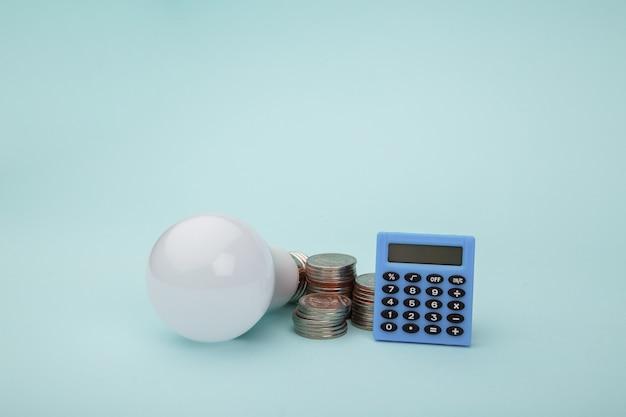 Лампочка с стеком монет и калькулятором. концепция энергии энергии