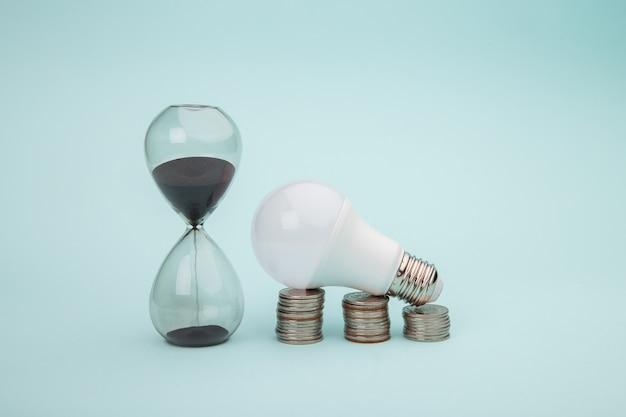 Лампочка с монетами стек с песочными часами на синем фоне. концепция энергии энергии