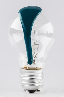 Light bulb with dripping green paint