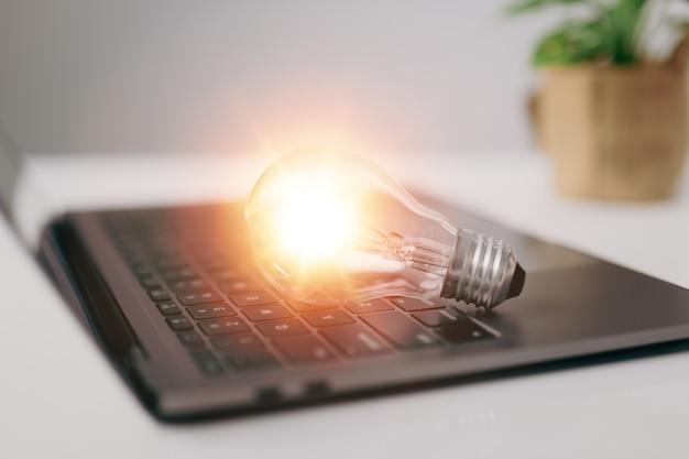 Лампочка с ноутбуком, инновационная идея, концепция идеи вдохновения из технологий