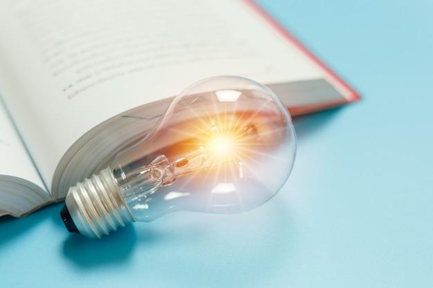 明るいフレアと本の青い背景の電球。創造性、アイデア、知識の概念について考える。