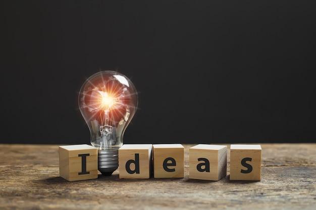ライトフレア付きの電球、木製のテーブルにアルファベットのテキスト「ideas」が付いた木製のキューブブロック。創造性、アイデア、創造的な概念のシンボル。
