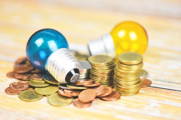木製のテーブルの背景に積み上げられたコインのランプからの光と電球