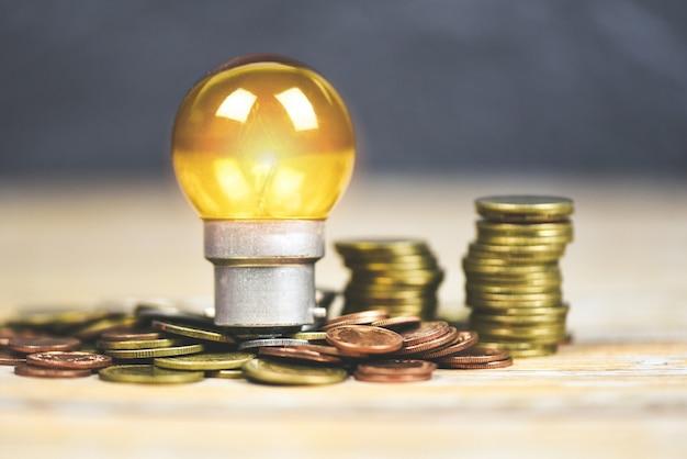木製のテーブルに積み上げられたコインのランプからの光と電球。省エネのアイデア、節電、世界の概念
