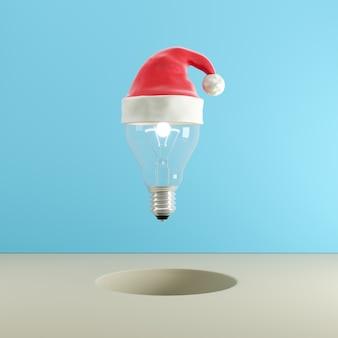 Light bulb with santa hat floating on blue