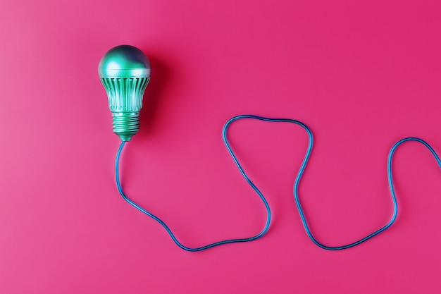 A light bulb with a wire isolated space on a pink wall. minimalistic style with conceptual ideas.