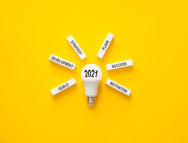 Light bulb with wooden blocks with plan goals for 2021 year