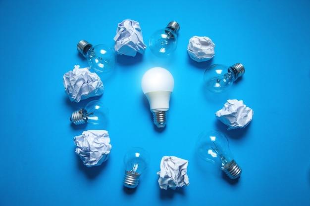 Лампочки и мятые бумаги на синем