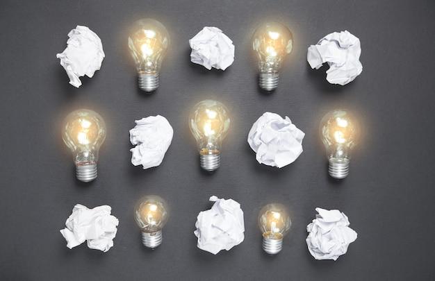 Лампочки и скомканные бумаги на черной поверхности