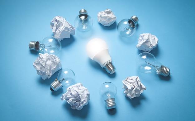 Лампочки и скомканные бумаги на синей поверхности
