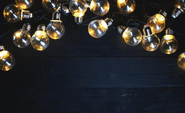 Light bulbs on black wood. top view copy space