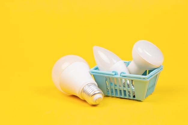 小さなショッピングカートの電球と彼女の下にある電球