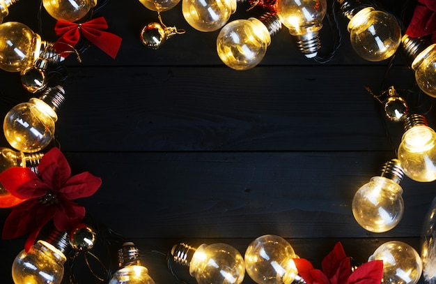 Light bulbs and red poinsettia on black wood. top view copy space
