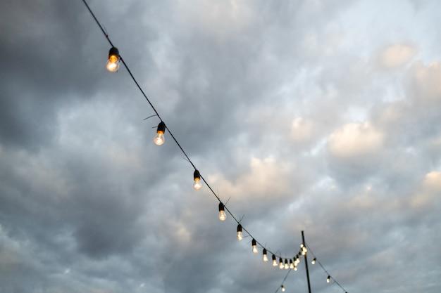 夕方に庭のレストランやカフェにぶら下がっている電球のレトロな花輪。照明の装飾。雲と明るい青空。ぼやけたバナーの背景
