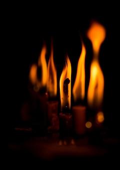 黒の背景で燃えているろうそく