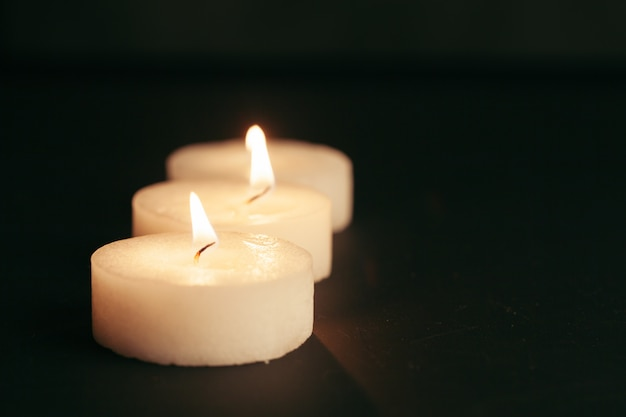 The light of the candle illuminates the darkness