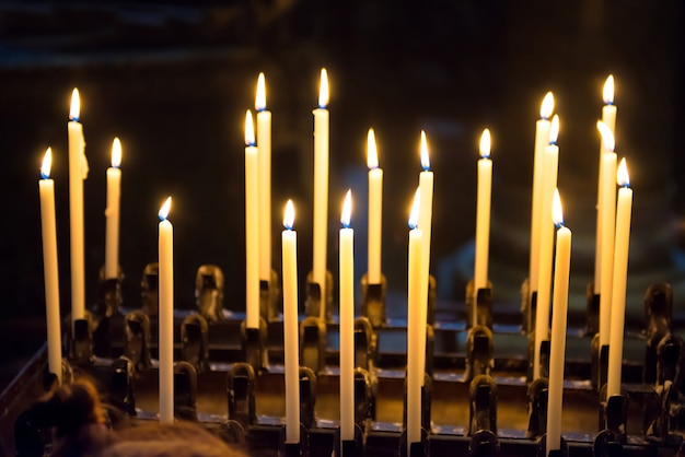 Light of candles in the church on the black background