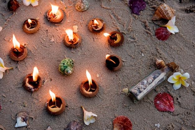 キャンドルや貝殻に火を灯し、貝殻や砂浜に設置されたボトルであなたがいなくて寂しいです。