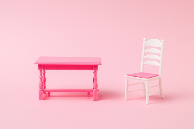 A light chair and a red table on a light pink surface