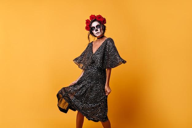 무서운 할로윈 마스크에 놀라운 라틴 여성의 모든 움직임과 함께 물방울 무늬의 가벼운 쉬폰 드레스가 흩어져 있습니다.