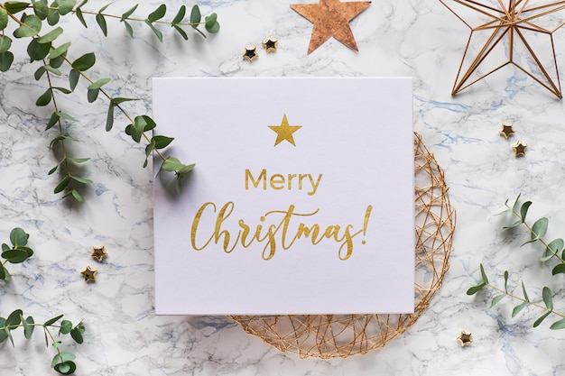 Light christmas frame with fresh eucalyptus twigs and golden geometric decorations. flat lay on white marble background with text happy holidays