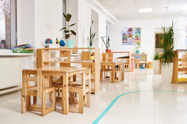 Light class kindergarten. wooden children's table with chairs in the foreground.