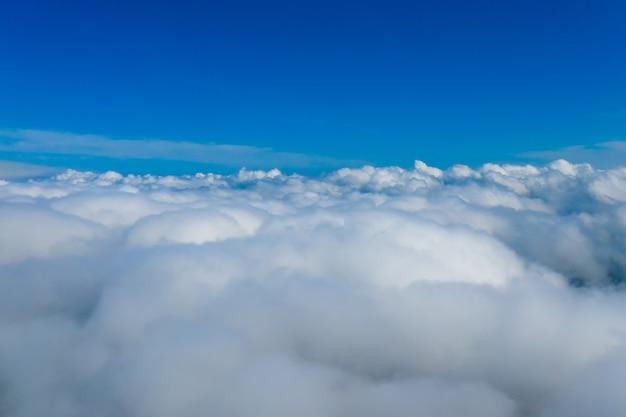 飛行機から見た明るい雲。ふわふわの雲の上の青い無限の空。