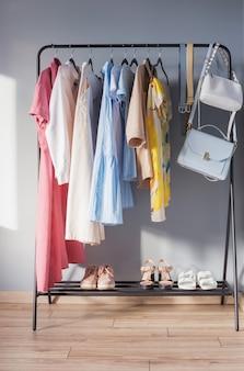 ハンガーに明るい色の女性の夏服と靴