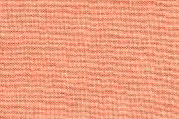 Light coral background from a textile material with wicker pattern, closeup.