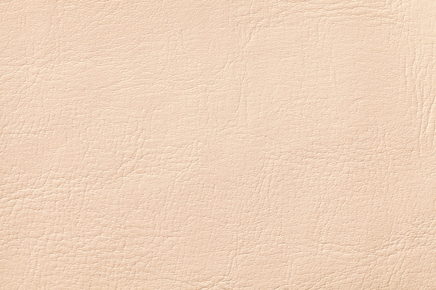 Light coral leather texture background, closeup. beige cracked backdrop