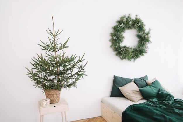 壁に花輪を捧げるクリスマスと新年のために装飾された明るく居心地の良いベッドルーム