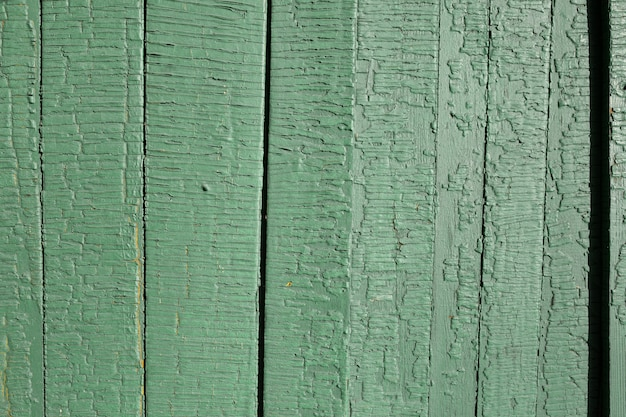 Light desaturated green, mint color old stressed, weathered, cracked rusic painted exterior timber planks plain background texture. trending color of the year 2020.