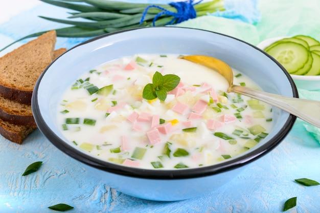 明るい背景のボウルにヨーグルトで味付けした、新鮮なキュウリの軽いダイエットスープ。