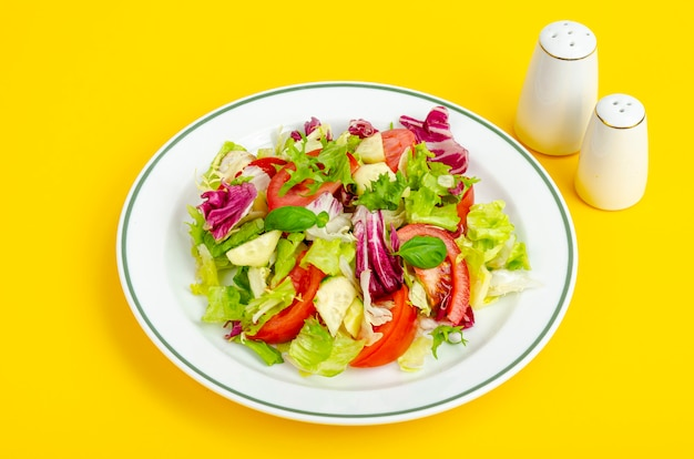 Light dietary vegetarian salad in plate on yellow table