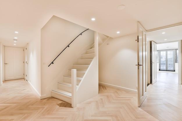 Светлый пустой холл и коридор с открытыми дверными проемами и паркетным полом в доме с лестницей, ведущей на верхний этаж.