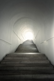 Light of the end of tunnel with ascending stairs
