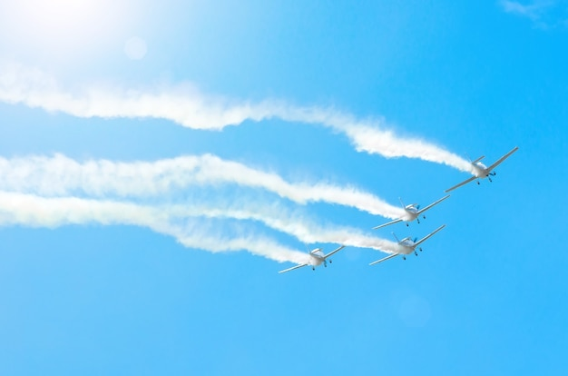 Light engine airplane with a trace of white smoke fly in groups in the blue sky with sunlight and glare.