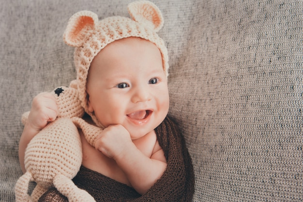 Light-eyed smiling baby. a little child in a beige cap with ears and a knitted beige toy in his hand