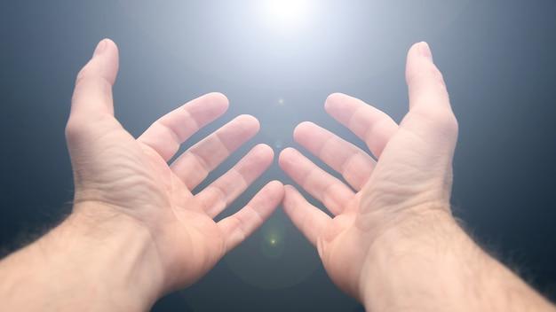 위에서 벌리고 뻗은 손에 빛이 떨어집니다.