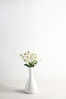 Light flowers in vase on table