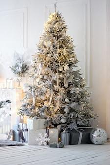 밝은 솜털 은색 크리스마스 트리, 회색 상자의 선물 및 밝은 방의 기타 장식