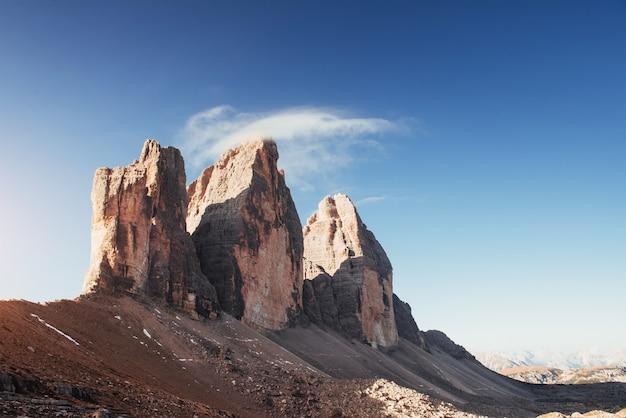 С вершин холмов начинает спускаться легкий туман. три вершины горы тре чиме.