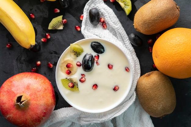 Light fresh yogurt in a ceramic bowl with small pieces of tropical fruits, kiwi, banana, garnet, grapess