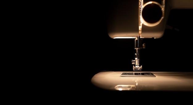 어둠 속에서 현대 재봉틀의 전구에서 빛
